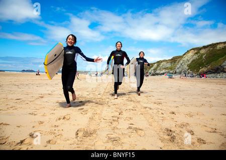 Beach Boys auf Gwithian Strand mit Godrevy Leuchtturm in der Ferne - Stockfoto