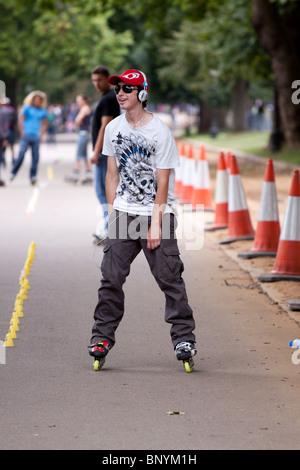 Ein männlicher Teenager selbst genießen mit Freunden an einem Wochenende mit Inlineskates im Hyde Park, London - Stockfoto