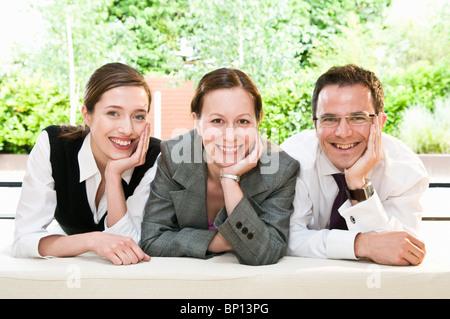 3 glückliche Kollegen Lächeln in die Kamera - Stockfoto