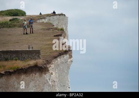 Wanderer an Spitze der vertikalen weißen Kreidefelsen in der Nähe von Beachy Head, Birling Gap, East Sussex, England, - Stockfoto