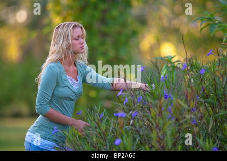Mädchen in der Natur, die Blumen pflücken - Stockfoto