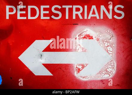 Fußgänger rotes Schild mit einem weißen Pfeil Bothways, aber eine mit weißer Farbe, London UK fast verdeckt. - Stockfoto