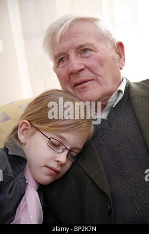 Enkelin zu ihrem Großvater kuscheln - Stockfoto