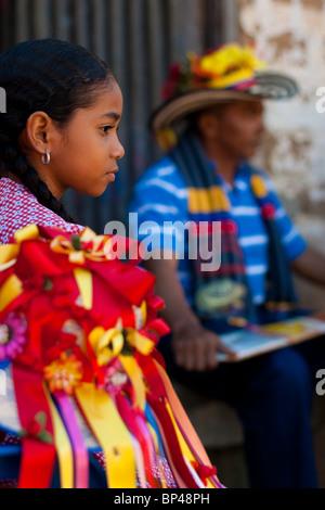 Ein junges Mädchen schaut Negros Tänzer während der religiösen Prozession in Atanquez (Sierra Nevada), Kolumbien. - Stockfoto