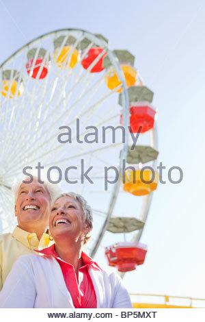 Älteres Paar im Vergnügungspark mit Riesenrad im Hintergrund lächelt - Stockfoto
