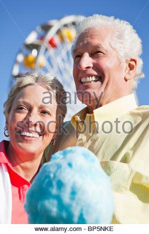 Senior paar Teilen Zuckerwatte im Freizeitpark lächelnd - Stockfoto