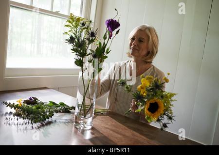 Reife Frau, die Vermittlung von Blumen - Stockfoto