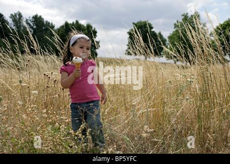 Zwei und eine Hälfte Jahr alt Kleinkind Essen ein Eis in einem Maisfeld - Stockfoto