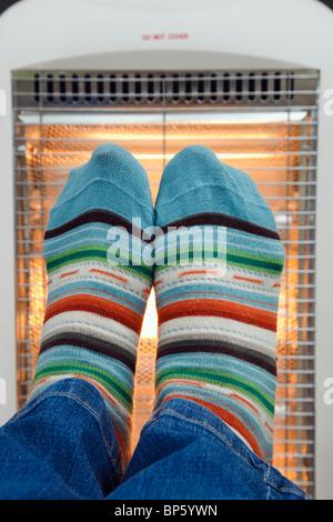 Person trägt bunte paarweise gestreift wollige Socken Erwärmung der Füße vor ein Niedrigenergie Halogen Zimmer Elektroheizung. - Stockfoto