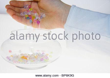 Eine Person, die bunte Perlen in ein Glas gießen - Stockfoto