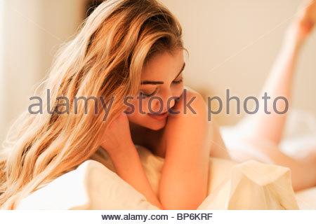 Eine Frau mit langen blonden Haaren, die auf einem Bett liegend - Stockfoto