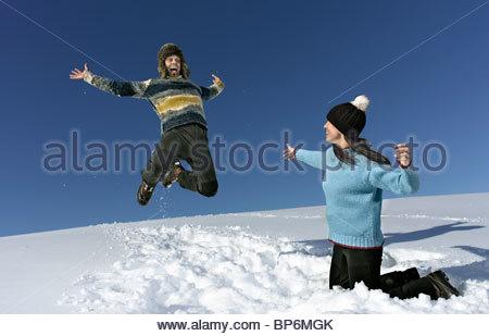 Mitte erwachsenes paar spielen im Schnee, Mann springt in die Luft - Stockfoto