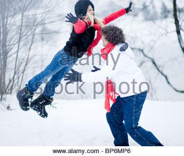 Junger Mann fangen junge Frau springen in der Luft am Wintertag - Stockfoto