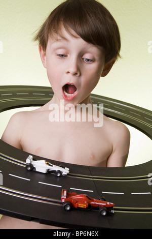 Ein Junge in der Mitte einer Spielzeug-Rennbahn beobachten das Spielzeug Rennwagen Rennen - Stockfoto