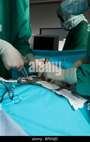 Ein OP-Team auf einen Patienten in einem OP-Saal, Fokus auf Händen - Stockfoto