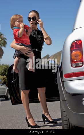 Eine Frau hält ein Kleinkind und Benutzung eines Mobiltelefons im stehen neben einem Auto - Stockfoto