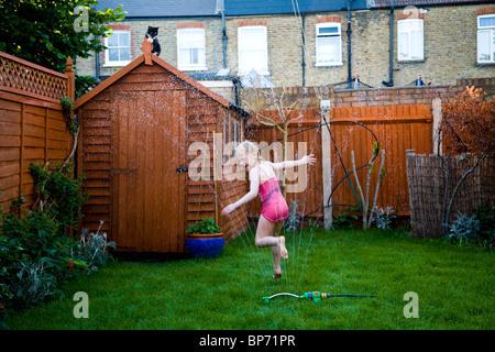 Junges Mädchen läuft durch Wasser Sprinkler in einem vorstädtischen Garten während versuchen, erfrischen Sie sich - Stockfoto