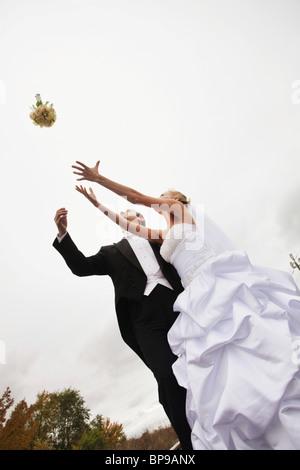 Stoney Creek, Ontario, Kanada; Eine Braut und Bräutigam, die versucht, einen Strauß zu fangen - Stockfoto