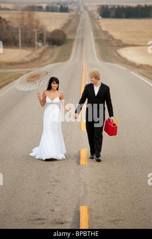 drei Hügel, Alberta, Kanada; eine Braut und Bräutigam zu Fuß auf einer ländlichen Straße hält ein Kanister und einem - Stockfoto