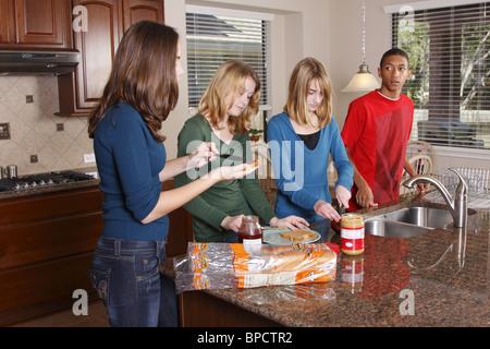 Teens machen Mittagessen, Erdnussbutter und Gelee sandwiches - Stockfoto