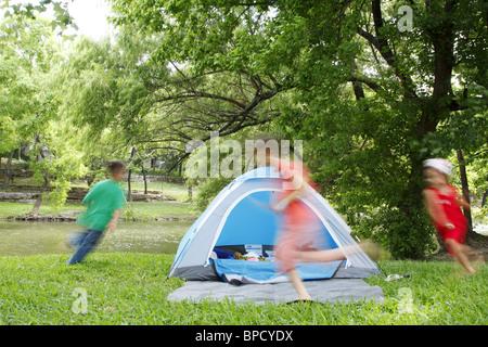 Kinder jagen einander um ein Zelt beim camping - Stockfoto