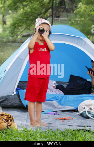 Niedliche Mädchen Blick in die Kamera durch Teleskop - Stockfoto