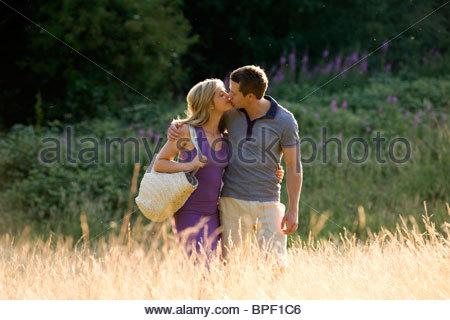 Ein junges Paar in einem Feld stehen, küssen - Stockfoto