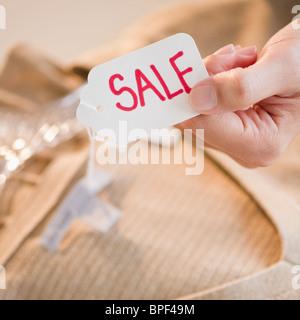 Hand hält Kleidung-Verkauf-tag