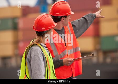 Transport-Ingenieure mit Containerschiff und Containern im Hintergrund - Stockfoto