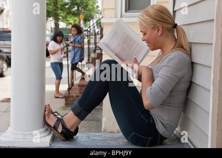 Spanische Teenager-Mädchen ihre Hausaufgaben mit ihrer Mutter und Schwester im Hintergrund, Boston, Massachusetts, - Stockfoto
