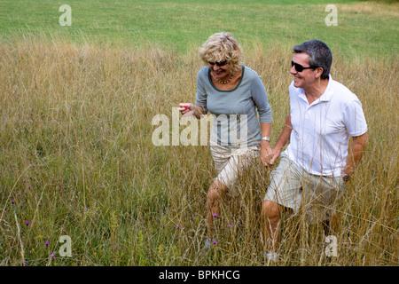 Ein paar Rentner, für einen Spaziergang durch ein Feld Hand in Hand. - Stockfoto
