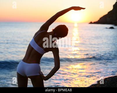 Schöne Brünette körperliche Übungen am Strand. - Stockfoto