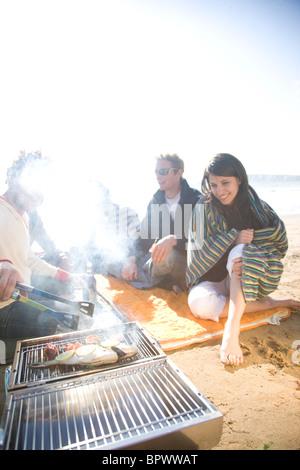 Gruppe von Freunden sitzen um ein Barbecue am Strand
