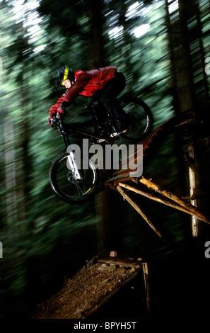 Ein Biker reitet auf seinem Mountainbike über eine hölzerne Rampe in North Vancouver, BC. (Bewegungsunschärfe) - Stockfoto