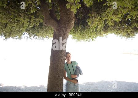 Junges Mädchen mit Kamera auf an Baum gelehnt - Stockfoto