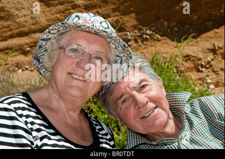 Älteres Ehepaar draußen sitzen auf einem Sommer Tag Lächeln. - Stockfoto