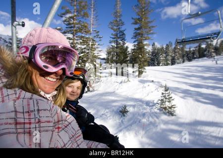 Junge Frau und Kind reiten Sessellift in Kirkwood, Kalifornien. - Stockfoto