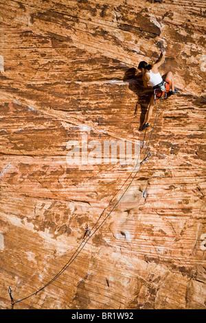 Eine Frau, Klettern an der Sandsteinwand des Calico-Becken in Red Rocks Canyon Conservation Area. - Stockfoto