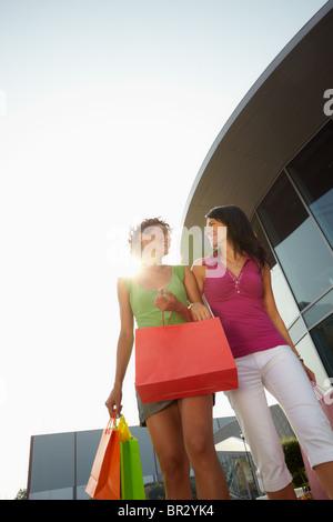zwei Frauen, die Einkaufstaschen tragen - Stockfoto