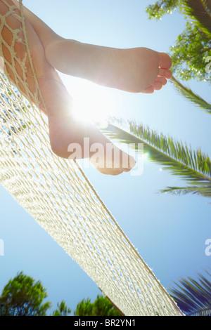 Blick auf Frau entspannen auf der Hängematte zugeschnitten. Niedrigen Winkel Ansicht, vertikale Form - Stockfoto