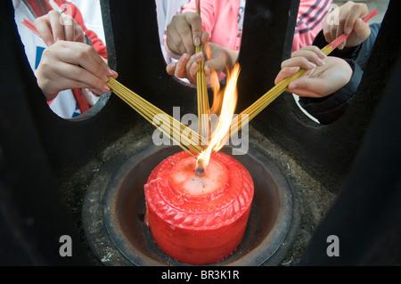 Teenie Mädchen leichte Weihrauch Pakete während des Besuchs, Wenshu Tempel, Chengdu, Provinz Sichuan, China - Stockfoto