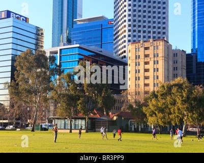 Büroangestellte, die Fußball spielen auf ihr Mittagessen in einem Park neben der Stadt zu brechen. - Stockfoto