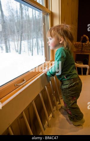 Ein kleines Mädchen schaut aus einem Fenster, Newry, Maine. - Stockfoto