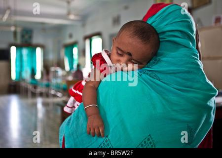 Eine Mutter bringt ihr Baby, das Kind In Not Institut Notfallstation. NGO führte medizinische Versorgung. - Stockfoto