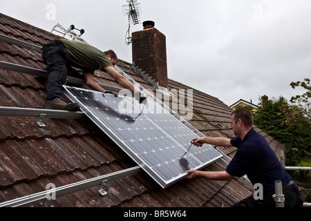 PV Photovoltaik Solarmodule auf dem Dach eines Hauses installiert werden. PV-Zellen wandeln Sonnenlicht in elektrische Energie. Stockfoto
