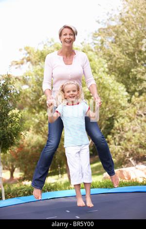 Mutter und Tochter springen auf dem Trampolin im Garten - Stockfoto