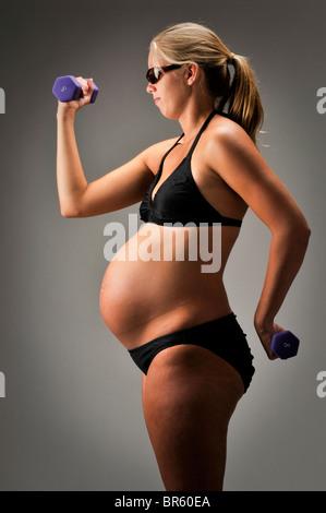Schwangere Frau mit Requisiten und schwarzen Badeanzug auf weißem Hintergrund. - Stockfoto
