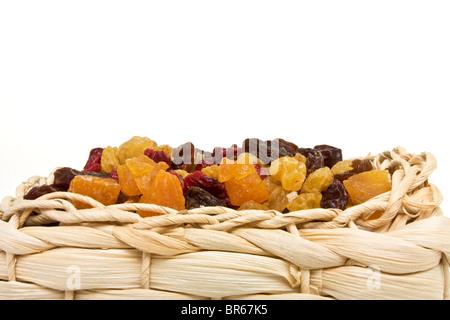 Gemischte Trockenfrüchte Aprikosen, Sultaninen, Rosinen und Cranberries in Weidenkorb. - Stockfoto