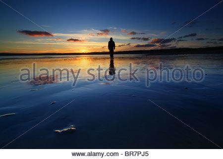 Silhouette eines Mannes, den Sonnenuntergang spiegelt sich im nassen Sand. - Stockfoto