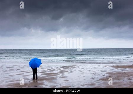 Eine Person, die einen blauen Schirm stehen am Strand mit einem dunklen Himmel Overhead; Newton, Northumberland, - Stockfoto
